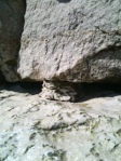A small rock burger holding up an entire cliff face